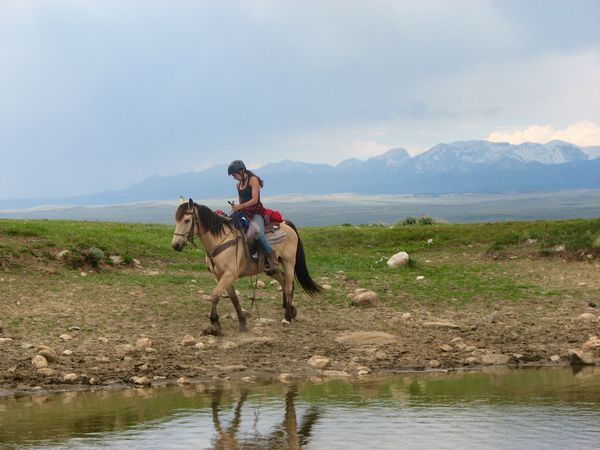 Horse packing student rides along the water's edge with mountains in the background.