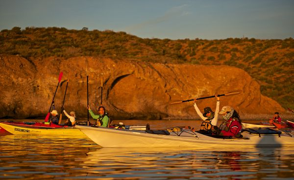 A group of female students out sea kayaking by rock bluffs at sunset on the Sea of Cortez in Baja California, Mexico.