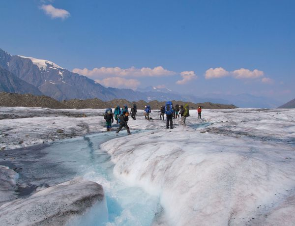 Students cross a glacier river in Alaska with towering snow-capped peaks in the distance.