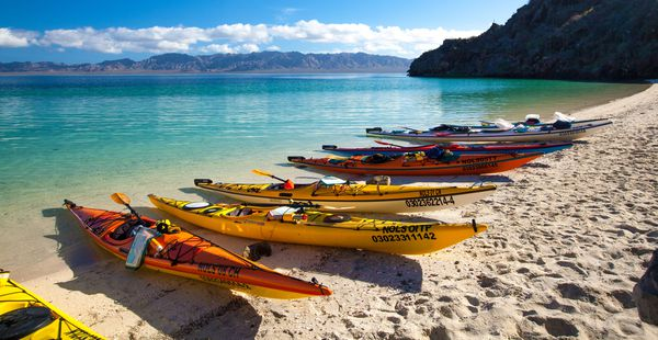 Kayaks beached on the shore by the turquoise waters of Baja California, Mexico.