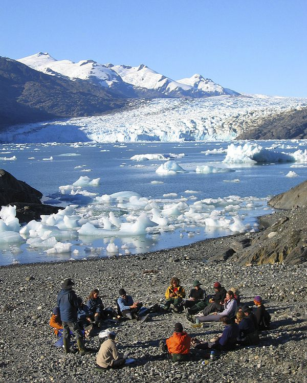 Circle of students gather around an instructor for a lesson in Patagonia with icebergs floating in the water behind.
