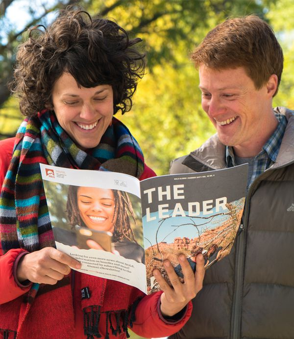 Two friends enjoying reading stories about NOLS grads in the Leader.