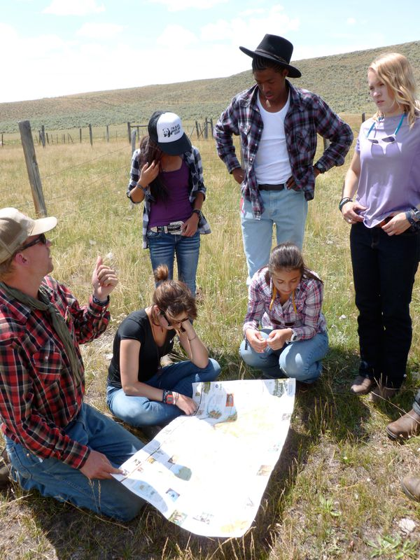 Horse packing participants gather together to consult a map.