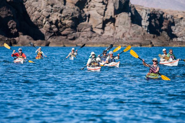 Students sea kayaking by rocky cliffs in the bright blue waters of Baja California, Mexico.