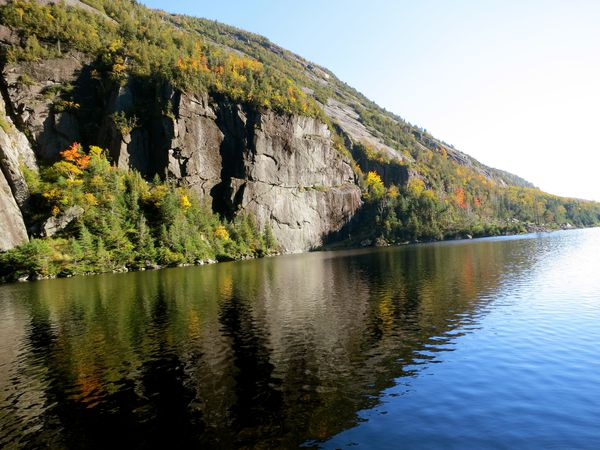 A lake in the Adirondacks bordered by steep cliffs and trees with fall foliage reflects the surrounding scenery.