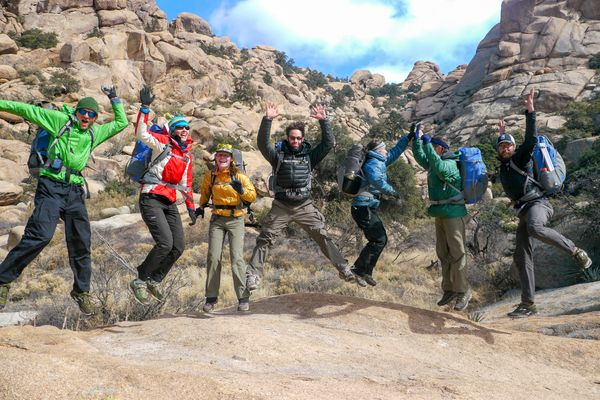 A group of students jumping amidst the rugged desert landscape of the Southwest.