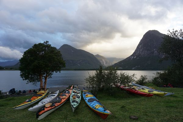A course's sea kayaks on the shore at sunset and the surrounding rugged mountains of Patagonia.