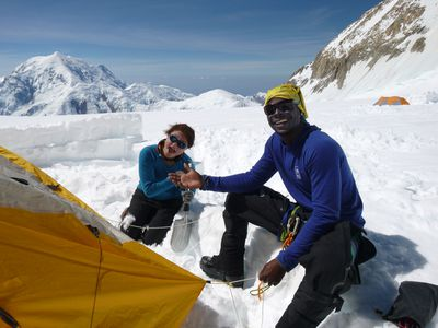 Two students have fun setting up a tent in the snow while mountaineering on Denali in Alaska.
