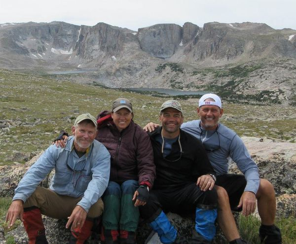 Four students on a NOLS Custom Education course smile together for a picture with mountains in the background.