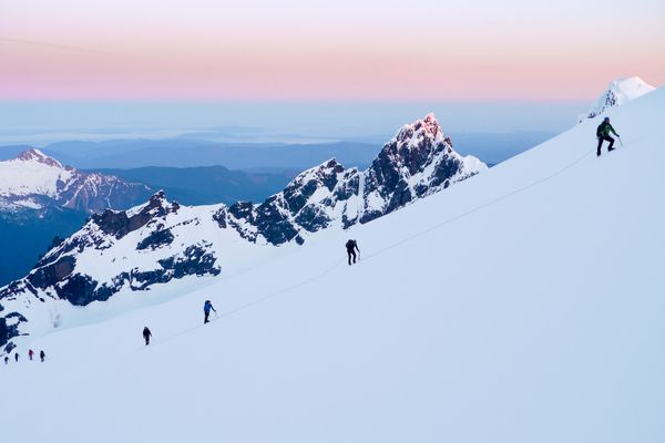 Students using their mountaineering skills to climb up the snowy Mount Rainier amidst stunning scenery at sunrise.
