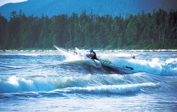 A course participant crests a large wave with a sea kayak in the waters of coastal British Columbia.
