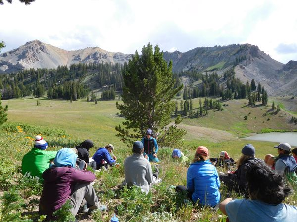 Instructor addresses a group of seated students on a grassy slope in the Wyoming Range of the Rocky Mountains.