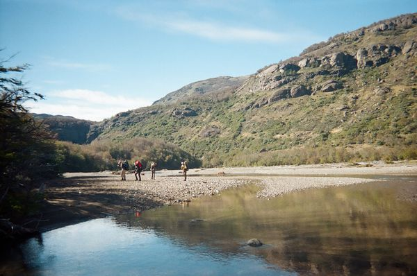 Four Kellogg Leadership course participants hike along a glassy waterway in Patagonia near base camp in Coyhaique, Chile.