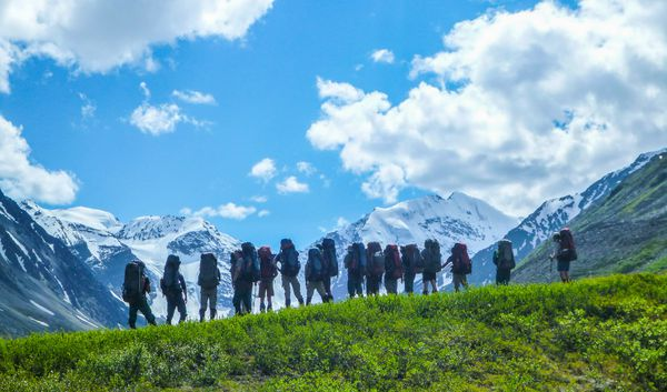 Students standing on a green grassy hill in Alaska - while out backpacking - and looking off to snow capped mountains in the distance.