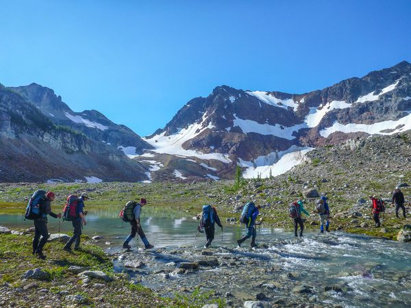 Naval Academy Mountaineering course participants cross a stream while backpacking.