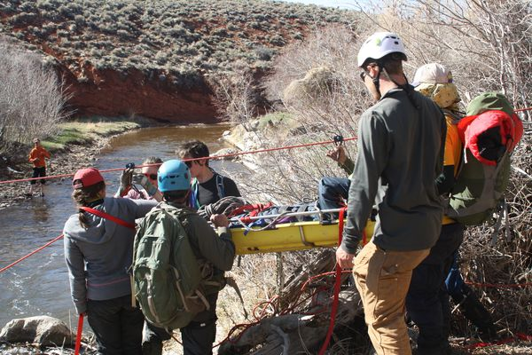 NOLS Wilderness Medicine students participate in a scenario in Red Canyon at the Wyss campus.