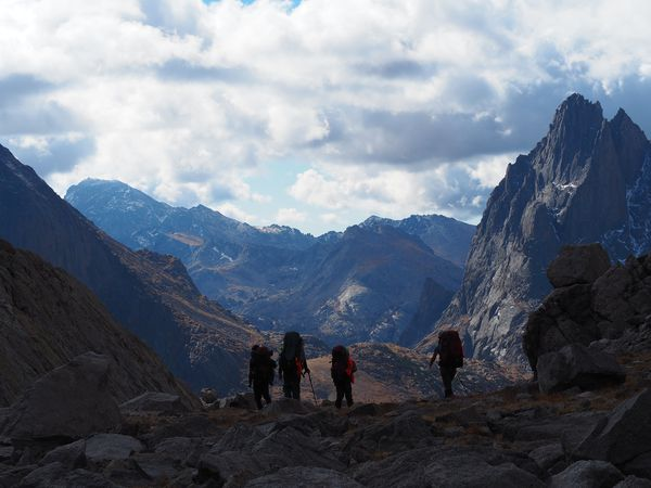 Students backpack down a rocky slope amidst towering, jagged mountain peaks in Wyoming's Wind River Range.