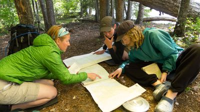 An instructor teaches students a lesson on maps in the backcountry of the Pacific Northwest.