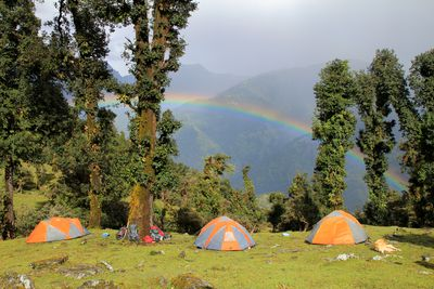 Student tents high up in the Himalayan wilderness beneath a brilliant rainbow.