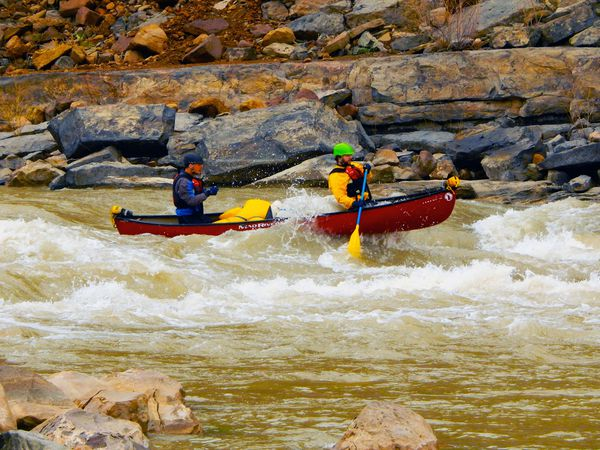 Students navigate a rapid while whitewater canoeing.